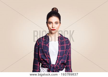 Confused or sad beautiful young caucasian woman with black bun hair frowning feeling bad after having done something wrong looking at camera with guilty and apologetic facial expression.