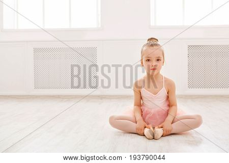 Portrait of little ballerina on floor, copy space. Smiling baby girl dreaming to become professional ballet dancer, classical dance school