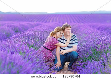 Romantic couple in love in lavender fields in Provence, France. Beautiful young man and woman hugging at sunset. Wedding or engagement