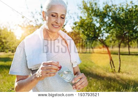 More active days. Positive senior smiling woman with a towel on the shoulders drinking water and resting after sport while standing in the park