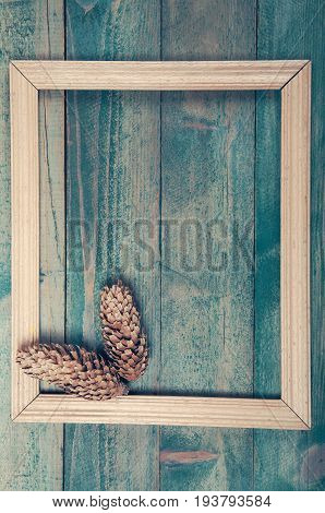 Photo frame with two pine cones on old wooden background