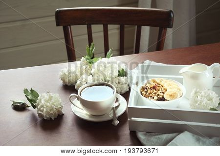 A healthy breakfast is a cup of black coffee with muesli sliced bananas and decor with flowers of viburnum. Side view.