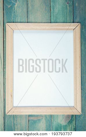 Blank wooden photo frame on wooden background