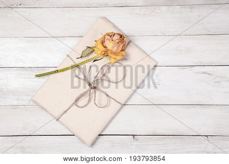 Paper wrapped package with dry rose on white wooden background