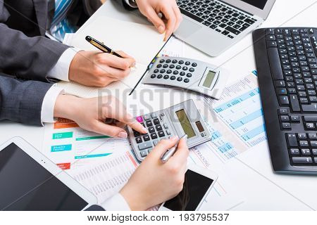 Business people laptop human hand stock market focus on foreground bank account