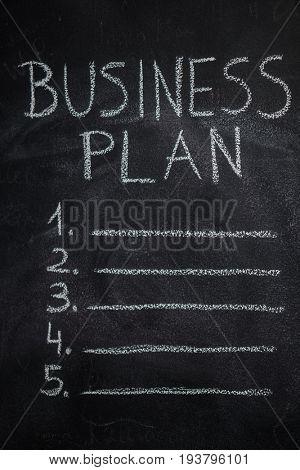 Business plan list written with white chalk on blackboard. To do list concept