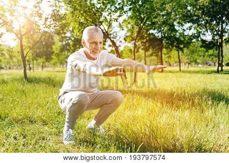 More active exercises. Positive aged man smiling and doing squats while enjoying sport exercises