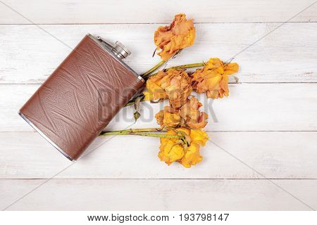 Hip flask with dryed roses on old white wooden background