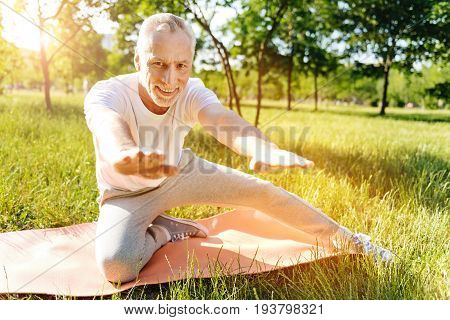 Upbeat mood. Cheerful retired man smiling and doing sport exercises in the park