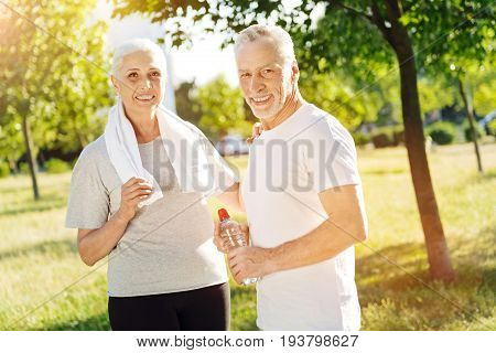 Stay active every day. Positive loving aged couple standing in the park and getting ready for sport exercises while expressing joy