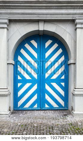 Old wooden door with white and blue stripes pattern in gray stone wall background texture. Luzern Switzerland