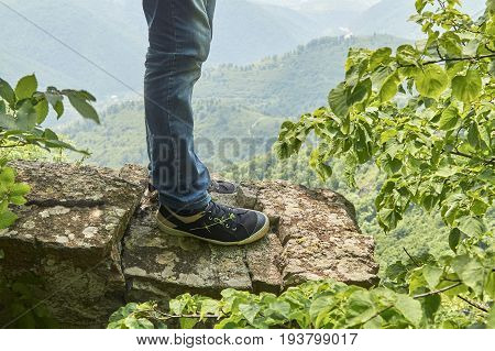 Male feet wearing sneakers standing on the precipice