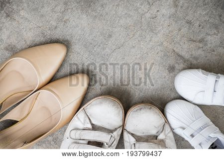 Shoes for parents and child on floor. Family concept