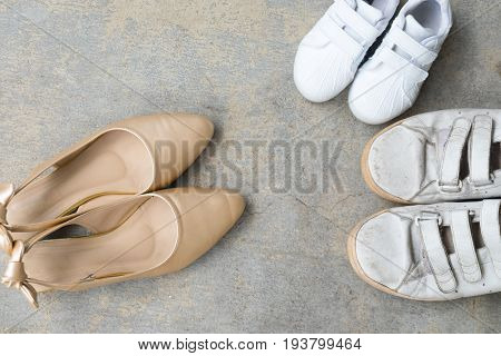Father shoes son shoes and mother gold high heel shoes on cement background family concept