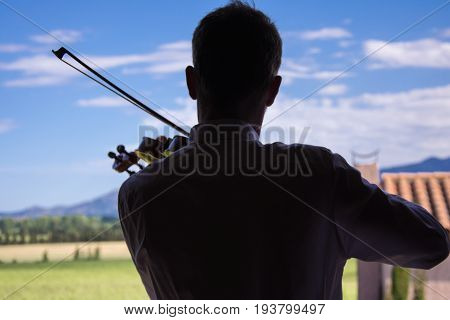 A backlit violonist playing in front of a sunny landscape