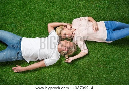 Above View Of Young Sweethearts Relaxing Together And Lying On The Grass