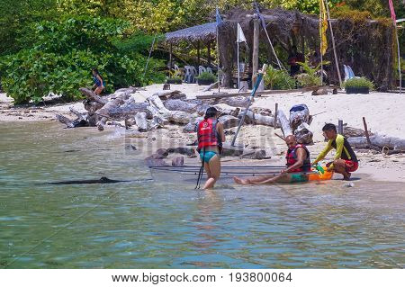 Labuan,Malaysia-May 1,2017:Group of tourist enjoying a weekend kayaking with the transparent kayak in Rusukan Besar island,Labuan,Malaysia.Labuan is the ideal place for water sports,like kayaking & scuba diving