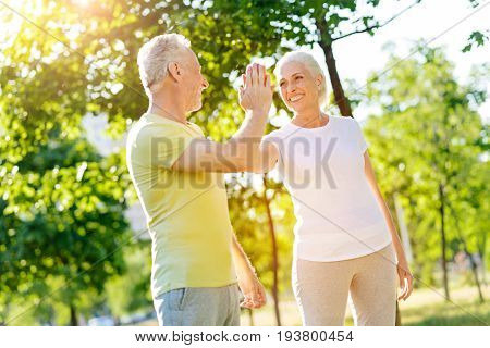 Good job. Cheerful senior couple smiling and giving high five while resting after sport exercises in the park