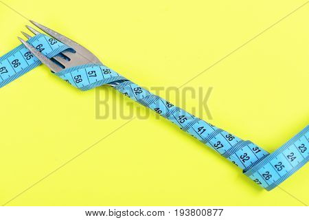 Silver Fork And Cyan Tape For Measuring Wrapped Around It
