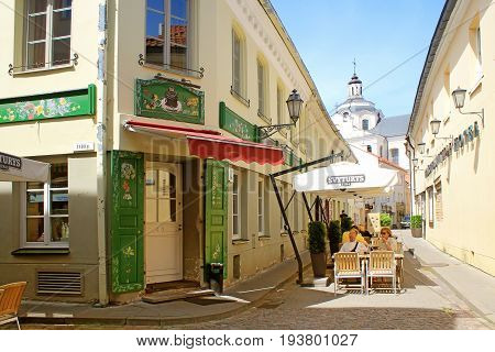 VILNIUS, LITHUANIA - JULY 18 2015: People relax at outdoor sidewalk cafe in the Old Town, Vilnius, Lithuania.