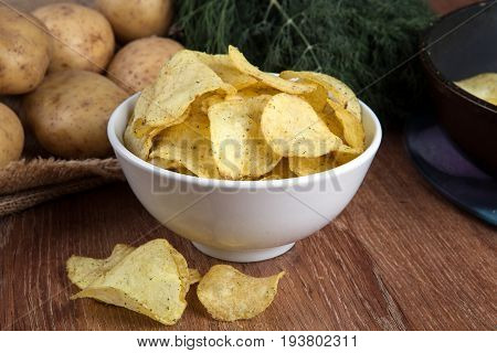 still life from a glass bowl with potato chips and vegetables close up