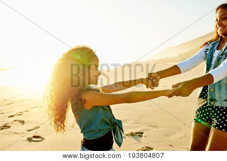 Two smiling sisters holding hands and spinning while playing on sandy shore in sunset lights.