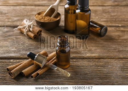 Composition with bottle of cinnamon oil on wooden background