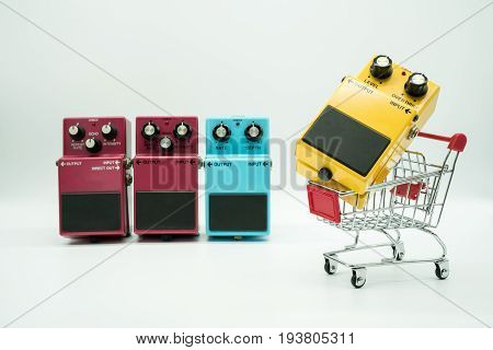 Group of vintage guitar pedals and shopping cart isolated on white background