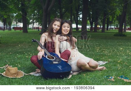 Young boho hippie girls play guitar in park. Friendship and fun