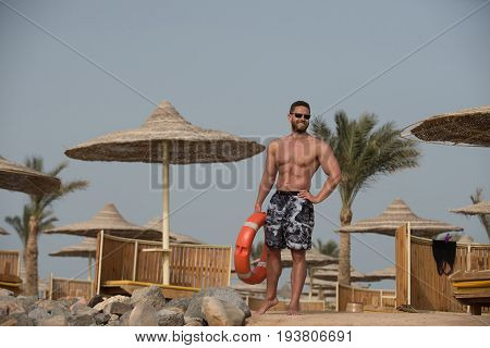 Man With Muscular Body Posing With Red Life Ring