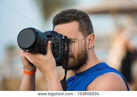 Man professional photographer with handsome bearded face holding his black digital camera equipment with closed objective lens