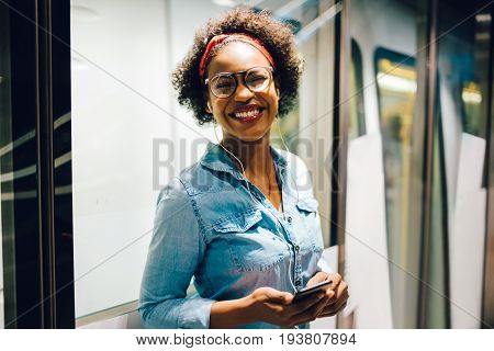 Smiling Young African Woman Listening To Music On A Train