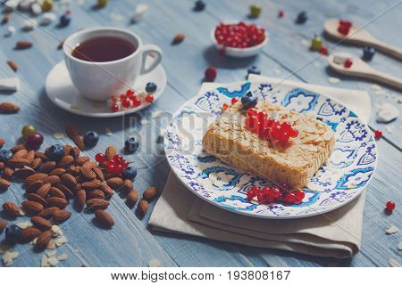 Sweet breakfast with pastry pie and berries - cowberry, red currant and bluberries. Beautiful food served at blue rustic wooden table, cake dessert at ethnic porcelain plate, almonds and tea cup.