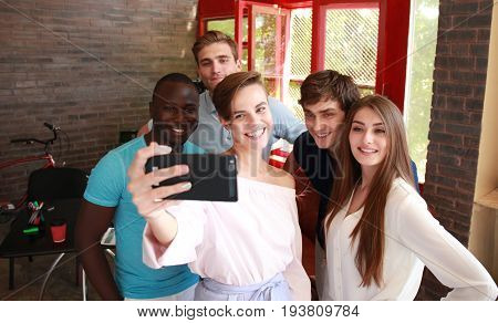 Group of colleagues taking a selfie in the office