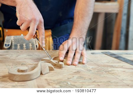 Carpenter with chisel in workshop, closeup