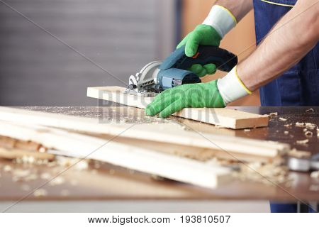 Carpenter working with electric saw, closeup