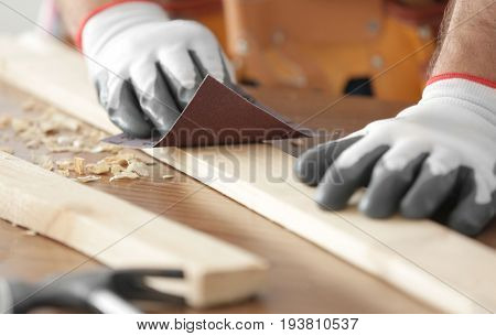 Carpenter sanding wooden plank on table, closeup