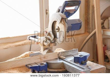 Circular saw and timber strip on table near window in carpenter's workshop