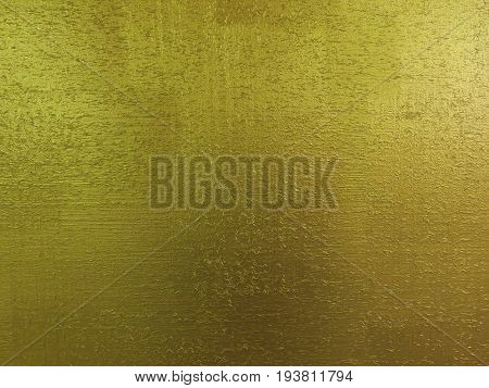 Yellow golden background texture with wooden sawdust particles like scratches. Brush painted wood surface. Golden pattern background. Golden plate gold painted wood wall