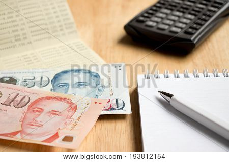 Bank passbook with Singapore dollar and book with pen calculator on wood table background