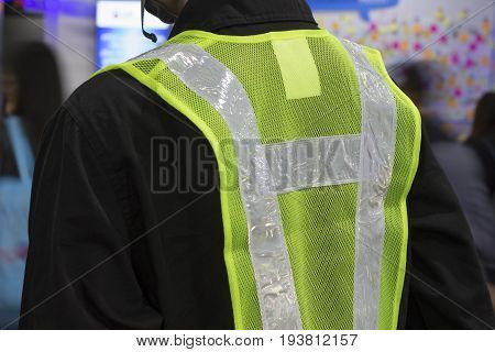 The back of a yellow mesh safety vest with reflective tape.