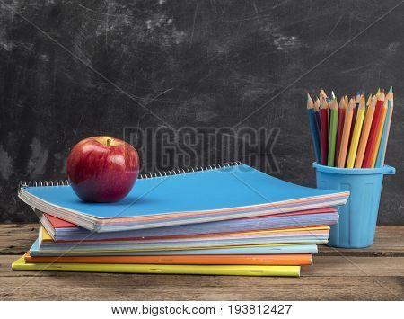 Notebooks on wooden table near chalkboard