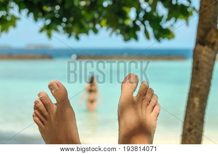 Man feet over blurred woman on beach. Travel, vacation and summer concept