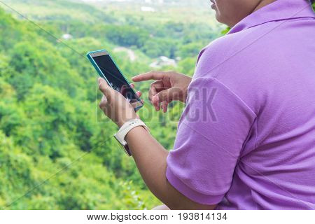 Hand Of Fat Asian Women Use Cell Phone Or Wireless Mobile Phone Over Mountain In Nature