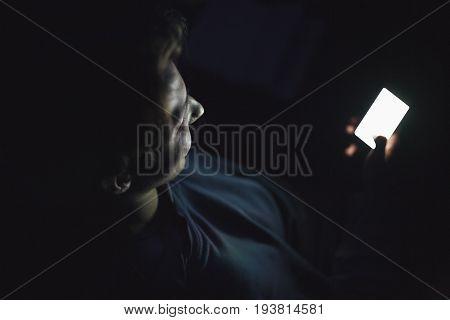 Happy teenage boy using smart phone in the dark