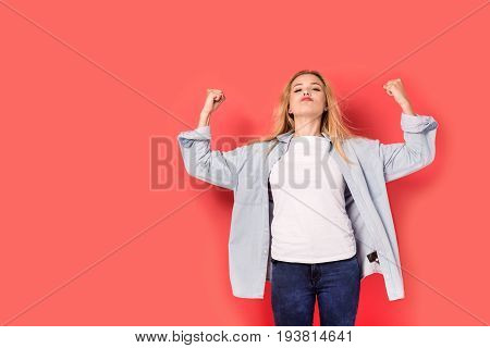 Young blonde girl shows her strength on red background. Picture including copy space for text