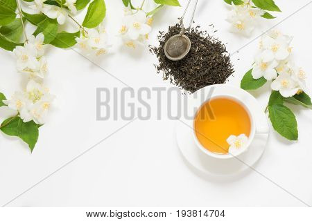 Jasmine dry green tea leaves with jasmine flowers and cup of tea on white background. Copy space and top view. Floral tea.
