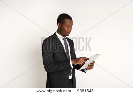 Smiling african american businessman using tablet. Young man in suit working with portable computer, isolated on white background. Business and modern technologies concept