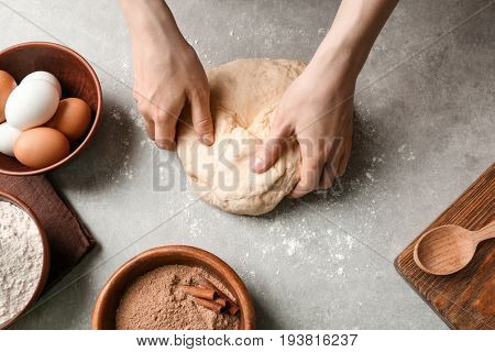 Woman kneading dough for cinnamon rolls on kitchen table