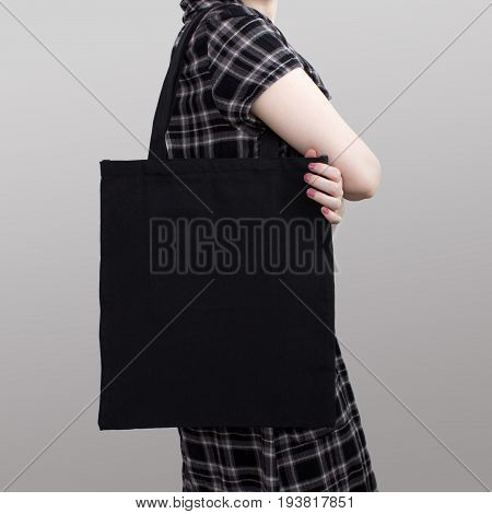 Mock-up. Girl in dress carries black cotton tote bag. Handmade eco shopping bag for girls.